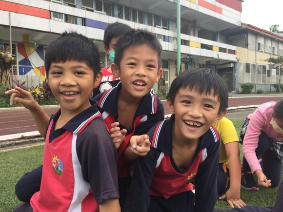 Three young children smiling for the camera in front of their school