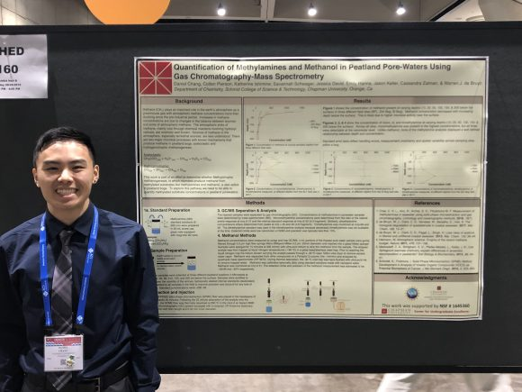 Chang standing in front of research poster