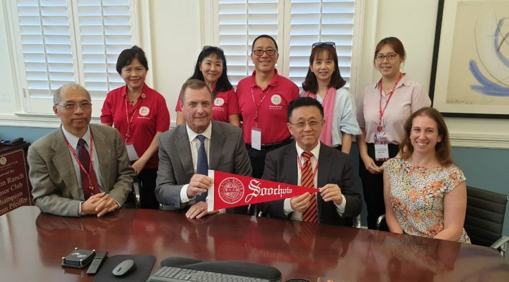 Soochow visitors holding Soochow banner with Dean Price and Assistant Director Jodi Hicks