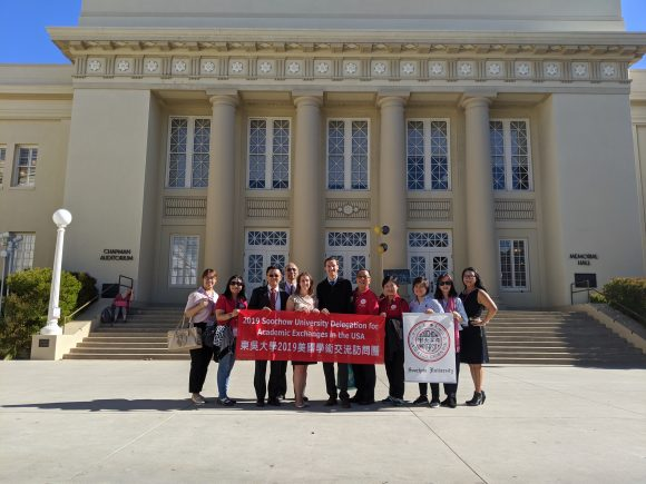 Soochow visitors and CGE students holding Soochow flag in front of Chapman library