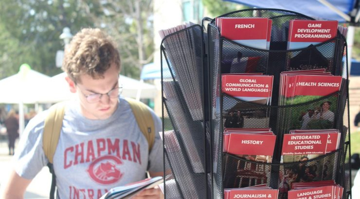 Student reading brochure, standing next to mobile shelf of other brochures with majors listed at study abroad fair.