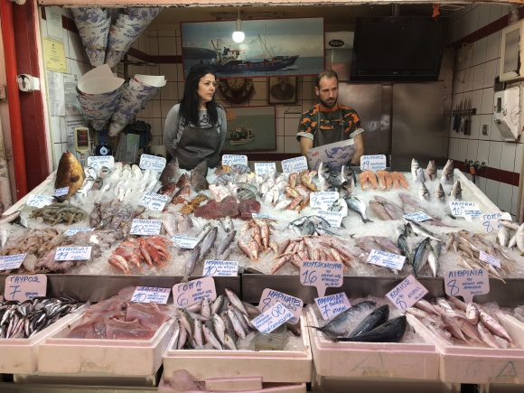 Food stand with variety of fish (red and grey, with skin and filleted, whole fish) over ice with 2 salesmen behind (female on left, male on right).