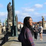Maia walking across a bridge in Prague. There is a chapel on the left-side of the bridge, a statue of a religious figure on the walkway, and people in the middle of the bridge. Maia is looking back and laughing with the sun in her eyes.