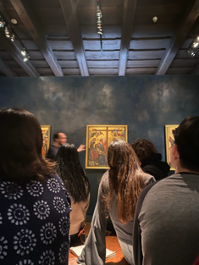 Art gallery. There is someone seemingly explaining a painting. The room is black, dimly lit, and the frame of the painting is gold. The painting is to far to see clearly. The photo is taken from the back of a room filled with about 10 people, some of whose backs block the picture from seeing other paitings around the room.