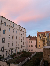 White building on the left with windows on each floor. Yellow building on the top of the photo with similar windows. The picture seems to be taken from the third floor of a building looking out into the street. The sky is cloudy and the clouds have a pink tint to them.