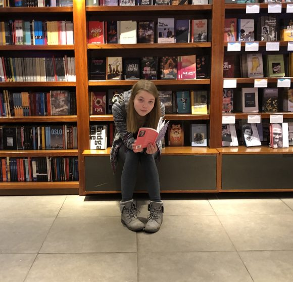 Student reading a book in front of book shelves