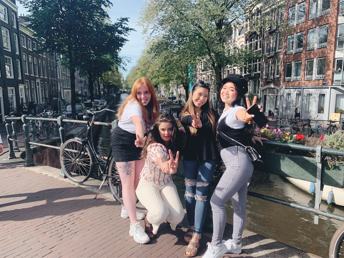 Rosa standing on a bridge and posing with three friends. On the left, a white womxn with red hair wearing a grey shirt and black shorts; her tattoo on her leg is revealed. Kneeling below her is another white womxn with brunette hair. Rosa stands inbetween them and another friend on Rosa's left, who is an Asian womxn. All of them are throwing up the peace sign.