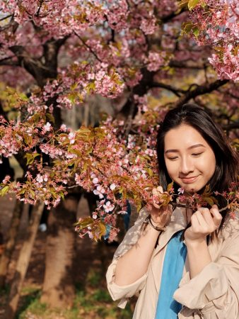 Lisa pulling down the branck of a cherry blossom tree and smelling the flowers.