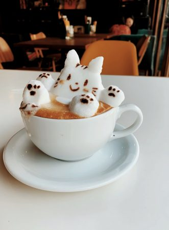 A cute coffee. White coffee cup on white place. Seemingly marshmallows on top of the coffee cup in the shape of a bunny taking a bath in the coffee.