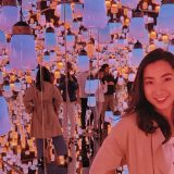 Lisa in an art musuem room filled with light bulbs hanging down from the cieling.