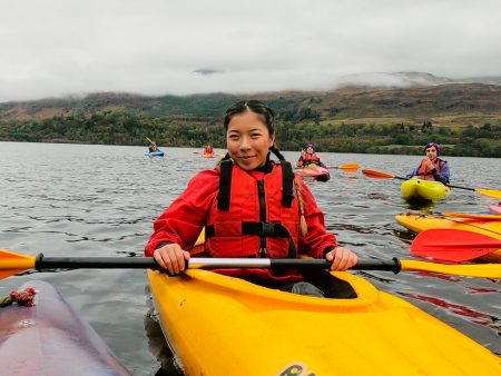 Rosa stopped on her kayak. Wearing a red life vest and a matching red wool sweater. Her hair is braided and she is smiling. Kayakers are featured in the background and the land is about a mile in the distance.