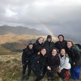 Rosa with friends on top of a mountain of beige/green grass fields. There are grey storm clouds in the background and rain in the distance. Sun shines through a hole in the clouds and a rainbow arches out behind the group. The group is primarily wearing black overcoats.