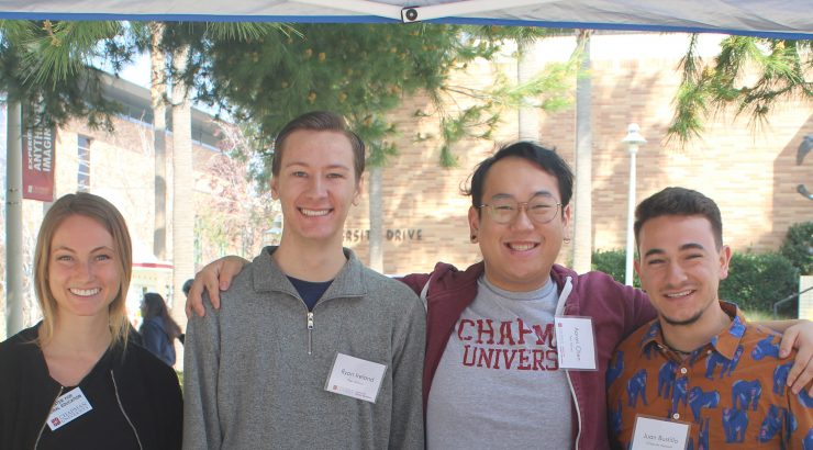 4 student workers standing at a table during study abroad fair. They are hugging each other, smiling, and looking at the camera.