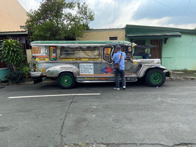 A man taking care of his Jeepney truck. The truck is long and maybe about 8 feet tall.