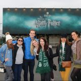 Talia witha group of friends in front of a Harry Potter billboard.