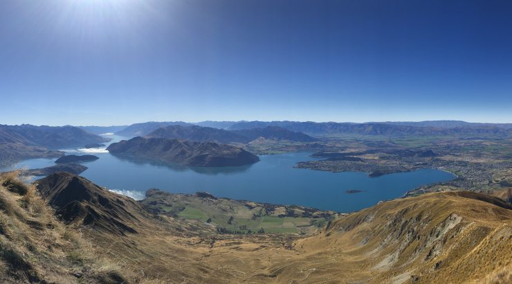 Panoramic photo of New Zealand including a lake with dark blue water and several small islands throughout.
