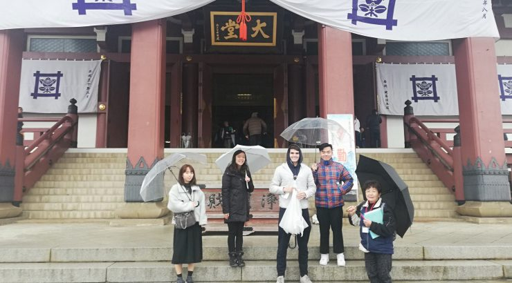 Students with umbrellas on steps in front of Japan temple