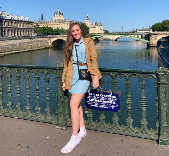 Student on bridge over water in Paris, France