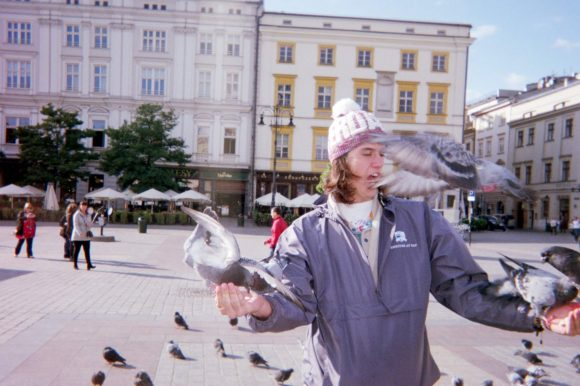 Student with pigeons in a plaza